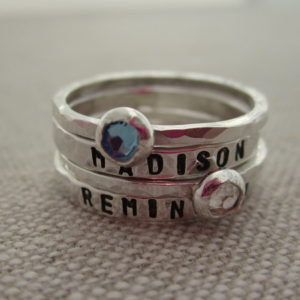 Silver stack rings with stones and names.